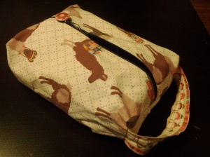 zippered, boxy fabric pouch, with llamas printed on it