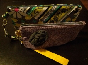 two zippered fabric wristlets with removable wrist straps